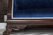 A wood bench upholstered in navy blue velvet with nailhead trim on a chevron painted floor