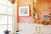 Red patterned wallpaper and an ornate gold mirror in a bathroom with white tile