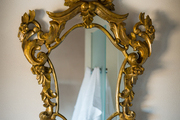 A gilded mirror hung against a white wall