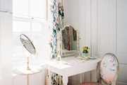 A white vanity and an upholstered chair set beside a window with floral curtains