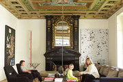 A living room with a frescoed ceiling, an ornate fireplace, and works by Jean-Michel Basquiat and Dan Flavin