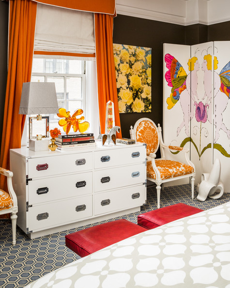 Eclectic Bedroom - A pair of upholstered armchairs flanks a white bureau amid colorful curtains and accessories