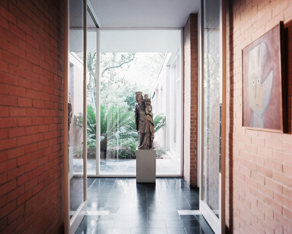 Entry - Brick walls and abundant windows in a home filled with art