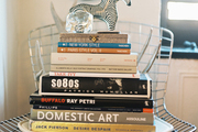 A metal Bertoia chair topped with a stack of books