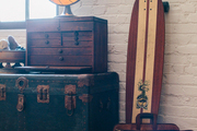 A collection of vintage items, including a steamer trunk, skateboard, lamp, and drawers
