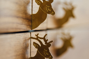 A detail of two gold deer hooks.