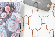 A wire organizer with tags and inspo images.