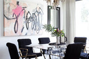 A modern piece of artwork hangs over a dining room table
