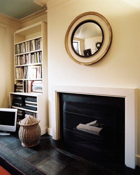 Fireplace - A convex mirror hung above a white mantel