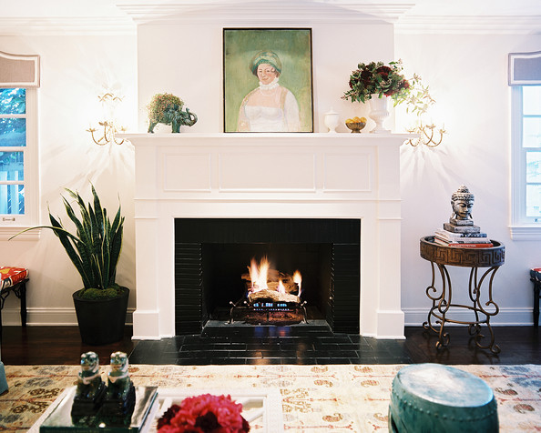 Fireplace - A patterned rug in front of a white mantel surrounded by plants and sconces
