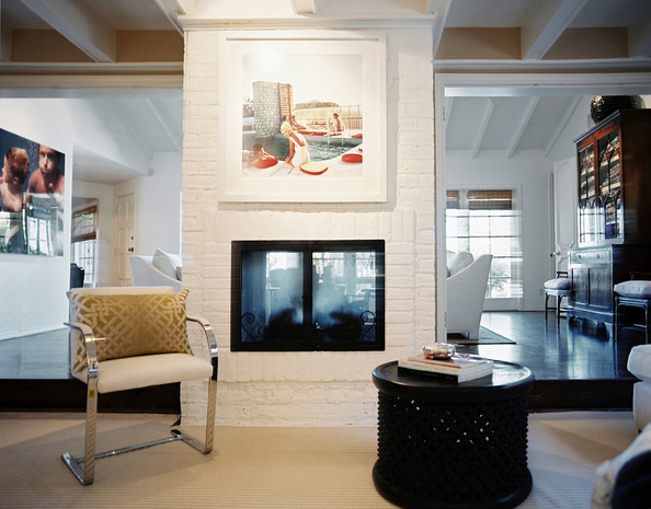 Fireplace - A white chair beside a two-sided painted-brick fireplace