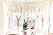 A contemporary dining room with beige curtains.