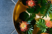 A brass bowl holds floating flowers and leaves