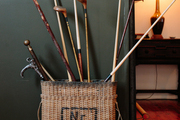 Antique golf clubs and pool cues in a vintage military carrier