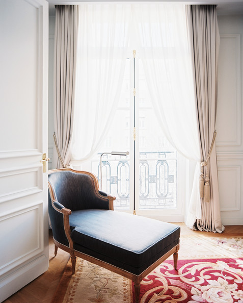 French - A chaise beside french doors leading to a balcony