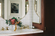 Classic bathroom vanity with round brass mirror, small bud vase, and marble countertop.