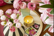 Pink flowers and a candle atop a table.