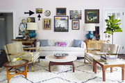A gallery wall behind a white sofa and rattan cabinet