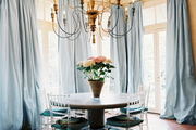 Lucite chairs surrounding a round table in a brick-floored breakfast nook