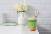 A detail of a green cup with toothbrushes in a white bathroom.