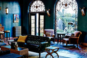 A moody hotel lobby with a chesterfield sofa, armchairs, and ornate windows