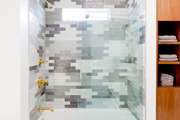 A gray tiled shower with blue and white tile floor.