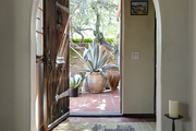 Large wooden door opens up to entry way.