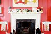 Disney-themed art above a mantel in a red-walled living space