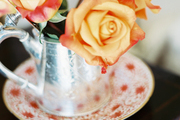 A silver teapot filled with roses on a wooden table
