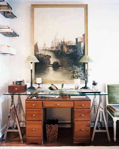 Glass Desk - A large framed artwork above a wooden desk and a glass-topped sawhorse table