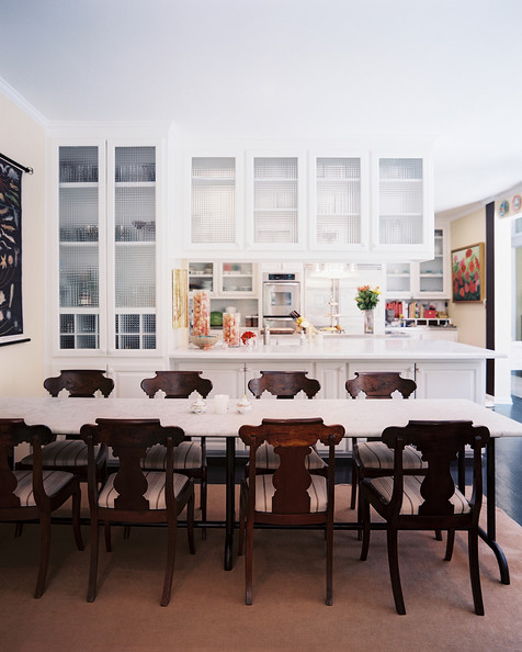 Glass kitchen cabinets antique wood chairs surrounding a sleek