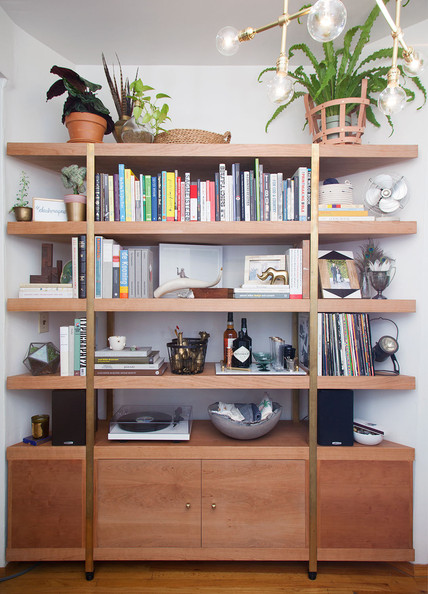 Gold Bookshelf - A custom-built shelving piece houses books, a record player, and assorted eclectic items
