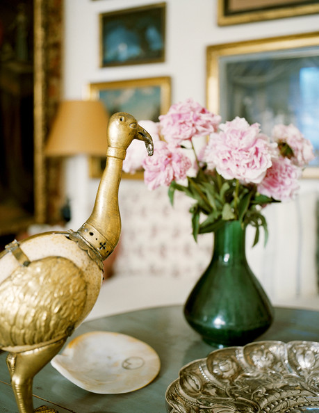 Green - A brass bird figurine, a silver tray, and a vase of flowers on a round table