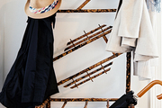 A bamboo coat rack covered with hats