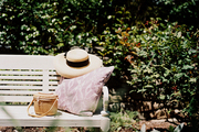 An outdoor bench, an ikat pillow, and a sun hat make for a quiet spot to read in Dominique Browning's Rhode Island garden.