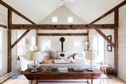 A soaring living room with exposed beams and whitewashed walls