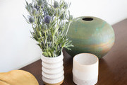 A grouping of decorative vases and a tray on a credenza.