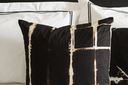 Black and white pillows atop white bedding.