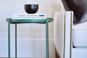 A detail of a green side table next to a gray couch.