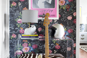 A bench and Lucite table paired with patterned wallpaper
