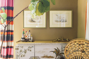 Dip-dyed drapery and an antique chinoiserie cabinet with a wicker peacock chair and a fiddle-leaf fig