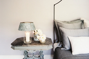 A candle lantern atop a gray bedside table