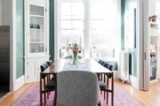 A contemporary dining room with a green wall and pink rug.