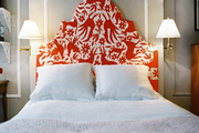 Sconces on either side of a headboard upholstered in a red Otomi fabric