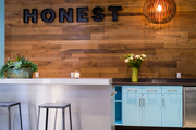 A kitchen with reclaimed wood and CB2's Peel Pendant Lamp at Jessica Alba's Honest Company office