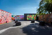Four boldly styled murals in contrasting styles in an outdoor space punctuated by tires