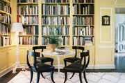 A tulip table and black klismos chairs surrounded by yellow built-in bookshelves