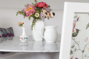 White vases with colorful flowers atop round white table.