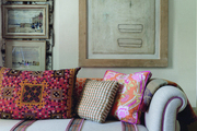 Patterned throw pillows atop a couch with plaid stripes in front of a gallery wall