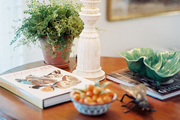A white lamp and a potted plant atop a round wooden side table